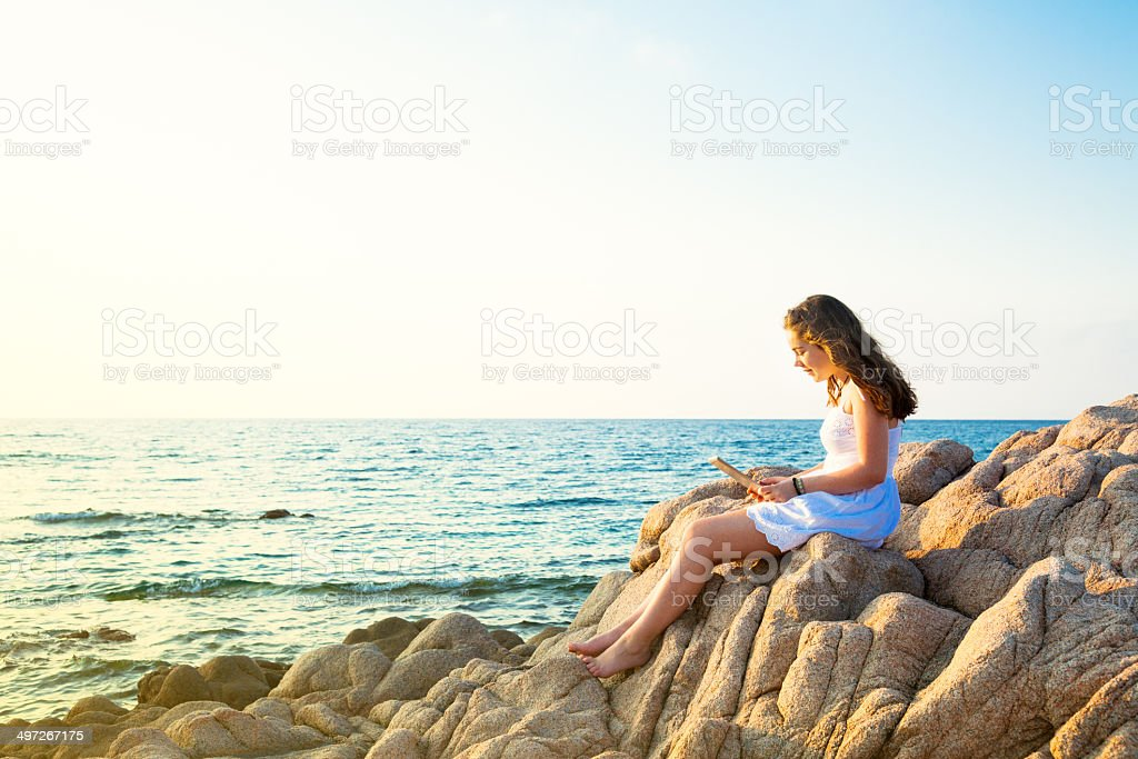 Girl on the beach with a tablet stock photo