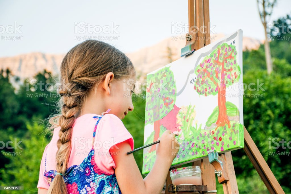 Girl On The Field Painting At Easel The View Of The Mountain - Close Up stock photo