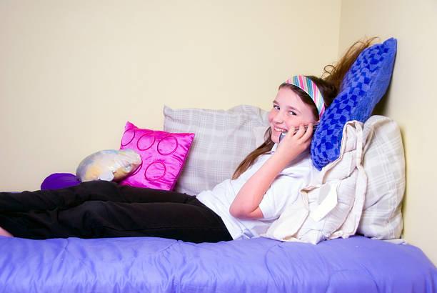 mädchen am telefon - lila teenschlafzimmer stock-fotos und bilder