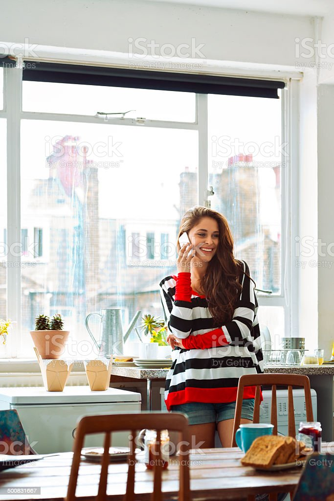 Girl on the phone Cheerful young woman standing in a kitchen at home and talking on phone. 20-24 Years Stock Photo