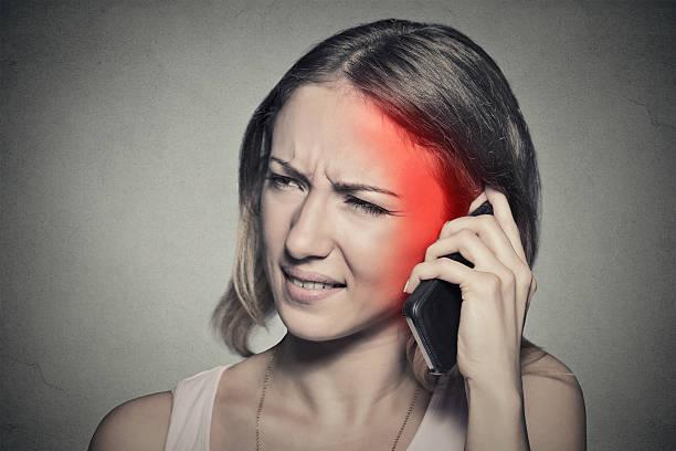 mädchen am telefon mit kopfschmerzen - strahlung stock-fotos und bilder
