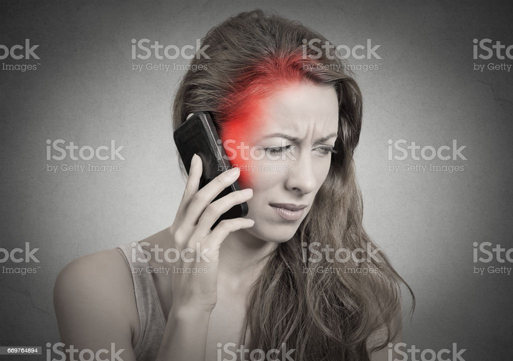 girl on the phone with headache. Upset unhappy female talking on phone stock photo