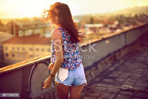 Portrait of a girl on a rooftop enjoying sunset