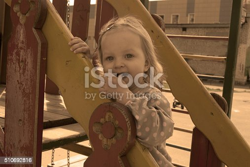 656743520istockphoto girl on the slide, with her finger in the mouth 510692816