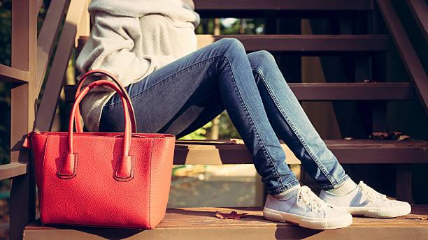 mädchen auf der treppe mit roten modische handtaschen - handtasche jeans stock-fotos und bilder