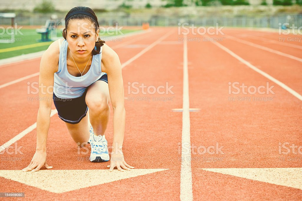 Girl on the track getting ready to run royalty-free stock photo