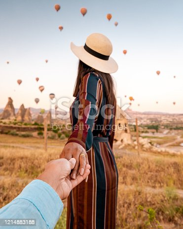 1035635902 istock photo girl on vacation at Cappadocia Turkey sunrise in the hills with hot air balloons, Kapadokya Beautiful vibrant colorful balloons in sunrise light in Cappadocia Turkey Goreme 1214883188
