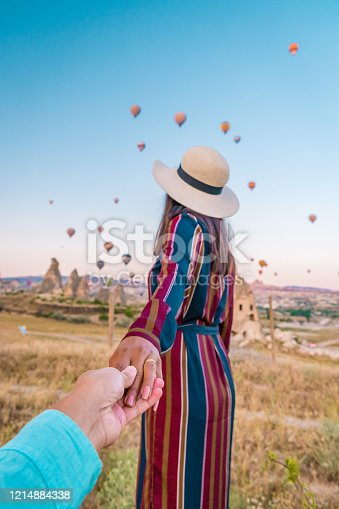 1035635902 istock photo girl on vacation at Cappadocia Turkey sunrise in the hills with hot air balloons, Kapadokya Beautiful vibrant colorful balloons in sunrise light in Cappadocia Turkey Goreme 1214884338