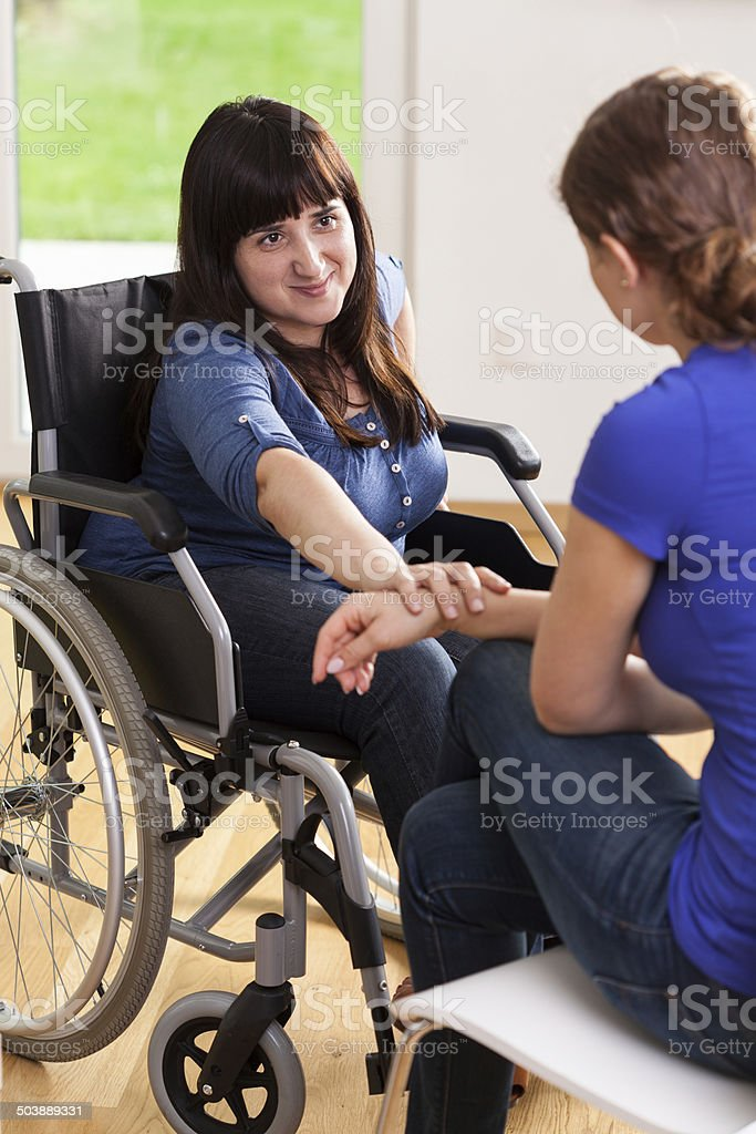 Girl on wheelchair talking with female friend stock photo