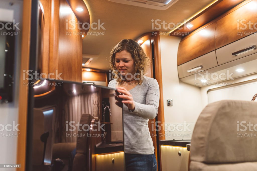 Girl opening a fridge in a luxury motorhome Girl opening a fridge in a luxury motorhome Adult Stock Photo