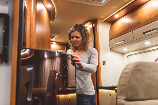 Girl Opening A Fridge In A Luxury Motorhome Stock Photo - Download Image Now