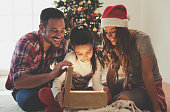 istock Girl opening a present on a Christmas morning withfamily 612223964