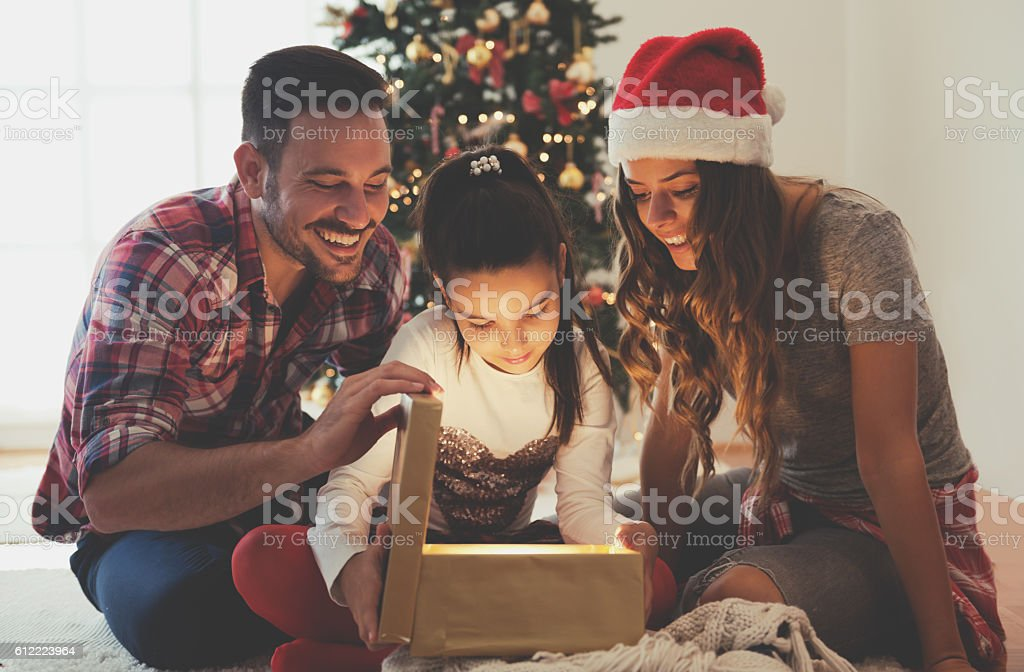 Girl opening a present on a Christmas morning withfamily stock photo