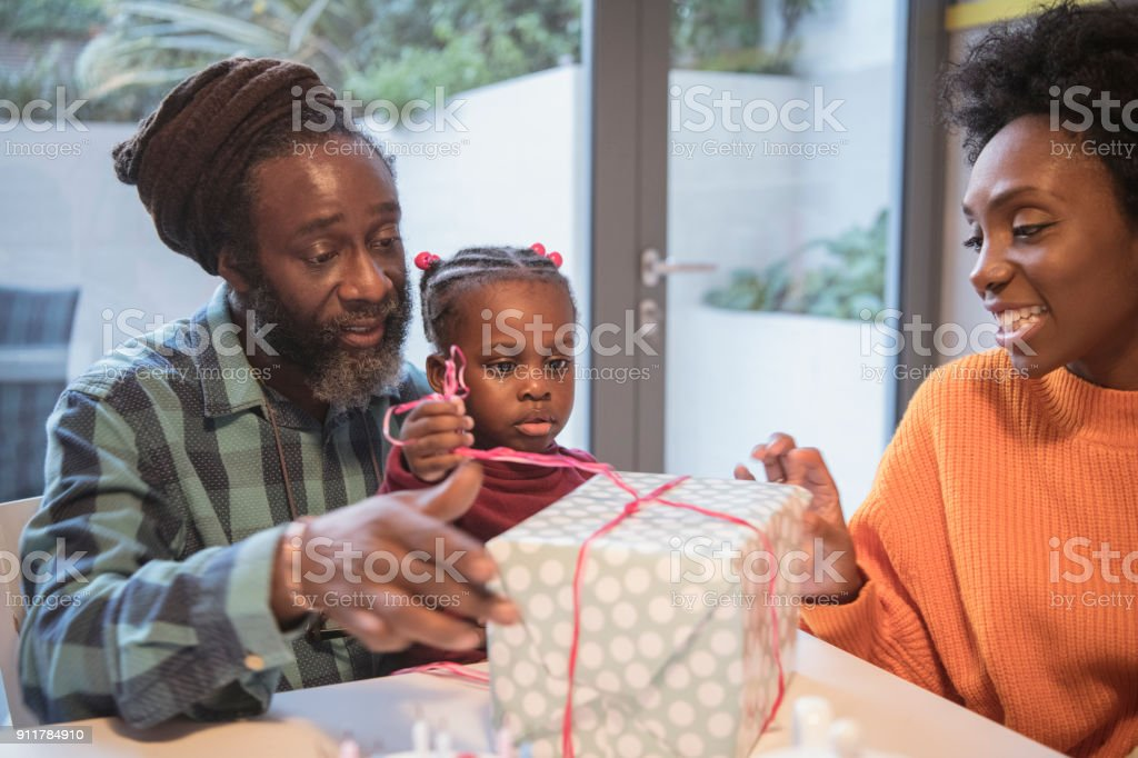 Girl opening birthday present with grandfather and mother watching stock photo