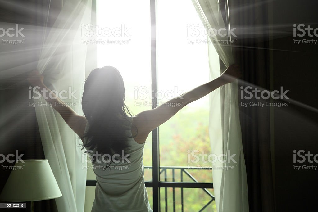 girl opening curtains in a bedroom stock photo