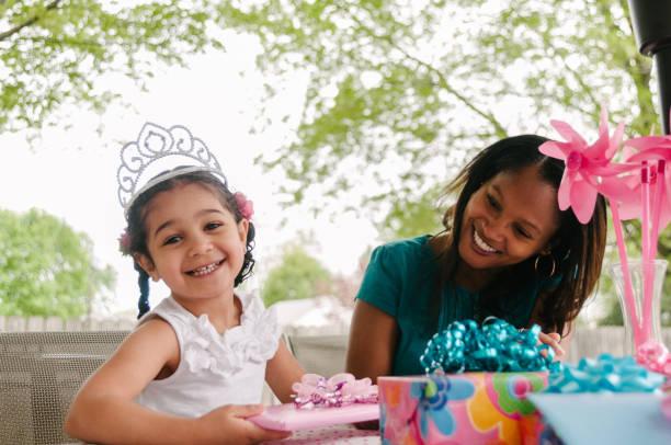 mädchen öffnen geschenke auf geburtstagsparty - prinzessin tiara stock-fotos und bilder