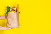 Food delivery or donation concept. Grocery store shopping. Girl or woman holds a paper bag filled with groceries such as fruits, vegetables, milk, yogurt, eggs isolated on yellow. Copy space