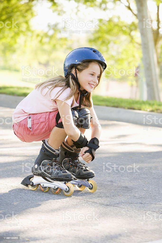 Girl outdoors on inline skates smiling stock photo