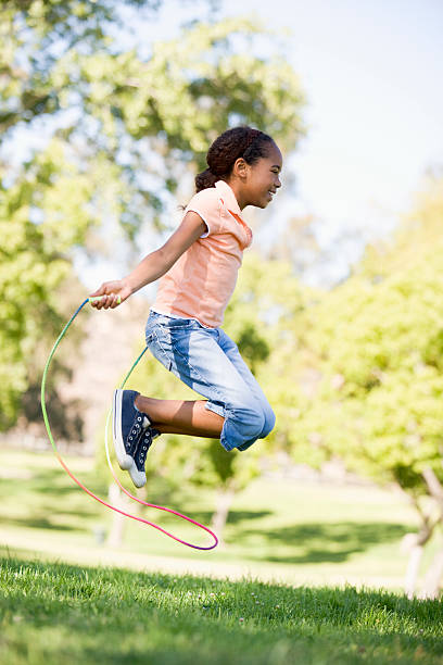 Girl outside using skipping rope stock photo