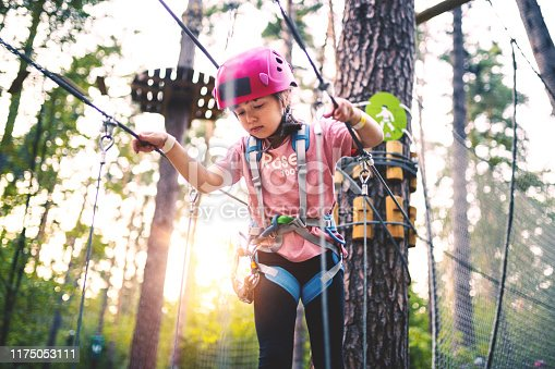 Girl overcomes obstacles in Adventure Rope Park