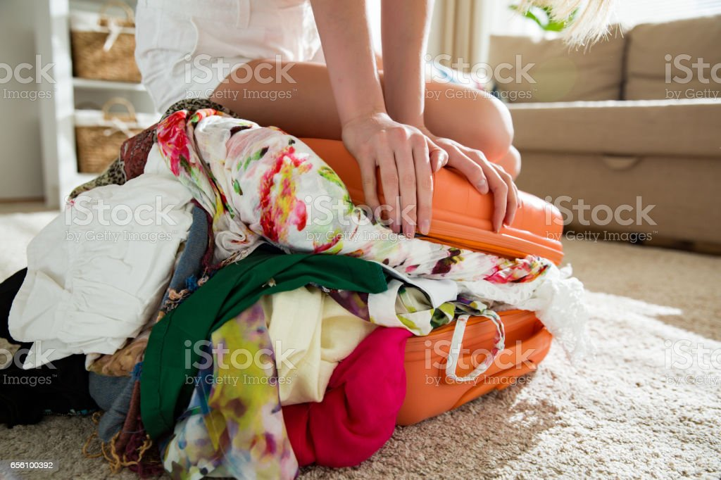Girl packing overflowing suitcase for travel​​​ foto