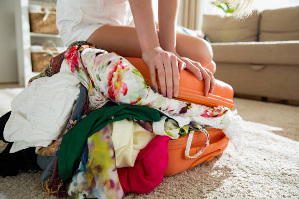 girl packing overflowing suitcase for travel - plein photos et images de collection