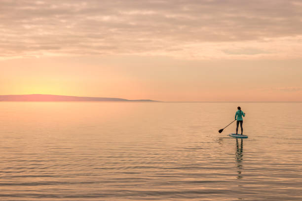 Girl paddling towards sunset stock photo
