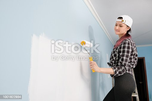 Young beautiful girl brunette painter, designer and worker paints a paint roller and brush wall. The wall is blue. Paint and brush, smile, works with satisfaction. On the model is an apron, a white tank top and a white baseball cap.