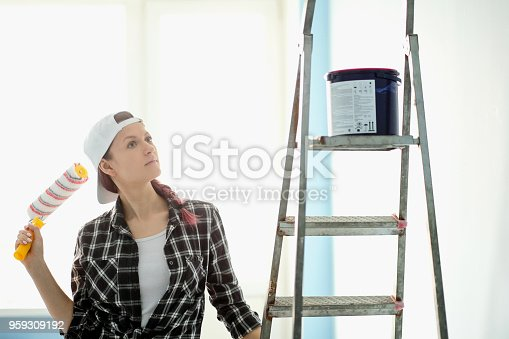 istock Girl painter, designer and worker paints a roller and brush the wall 959309192