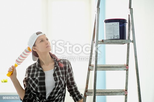 istock Girl painter, designer and worker paints a roller and brush the wall 959309252