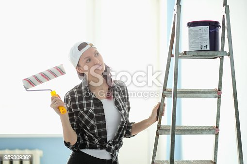 istock Girl painter, designer and worker paints a roller and brush the wall 959309362