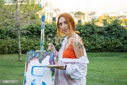 girl painter paints in the garden