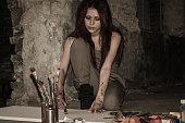 Girl painter working in the dark overtime