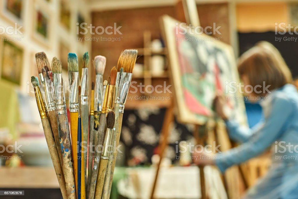 Girl painting a picture in art workshop stock photo