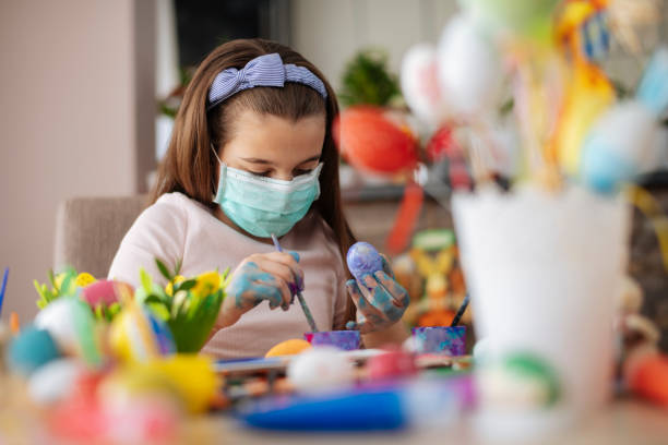 Girl Painting an Easter Egg with protective mask. Virus protection concept. stock photo stock photo