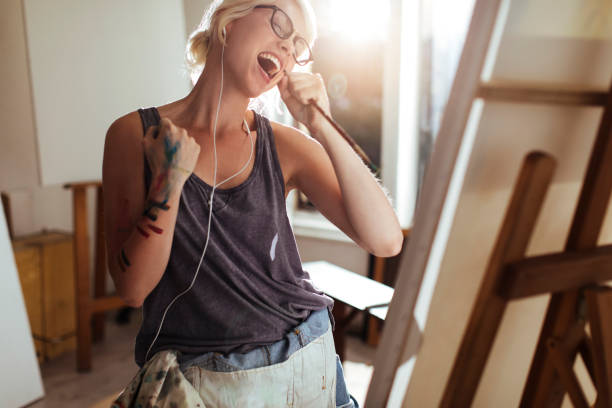 girl painting and listening to music - passion stock pictures, royalty-free photos & images