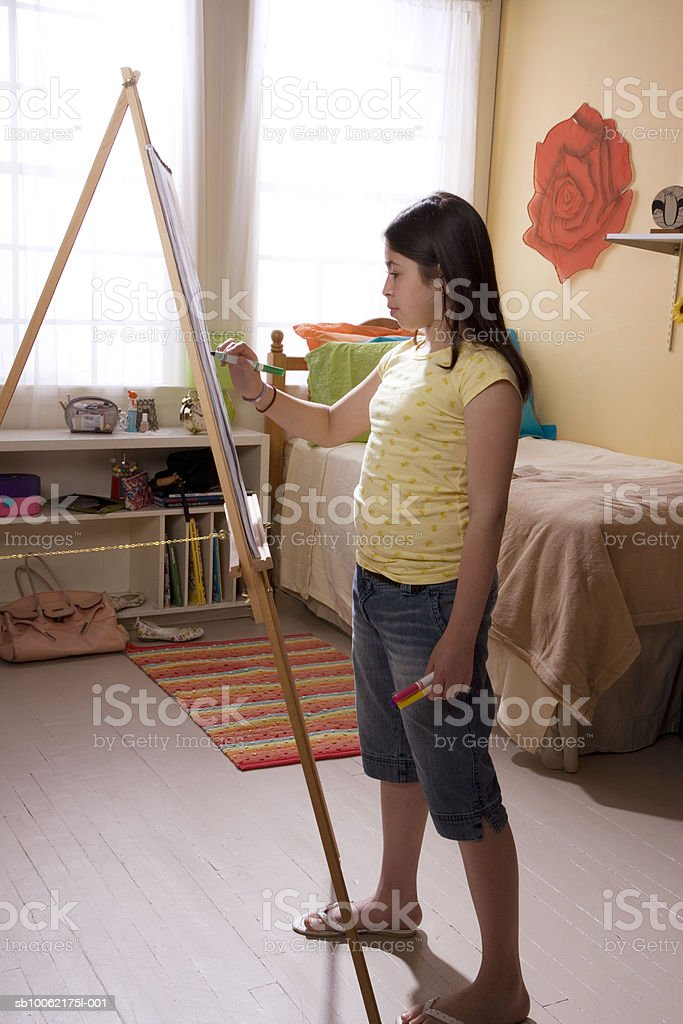 Girl (10-11) painting at easel, side view royalty free stockfoto