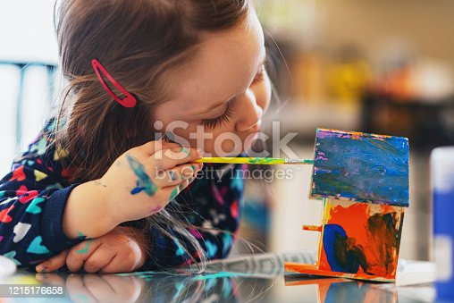 A three year old girl paints a tiny birdhouse with water colour paints.