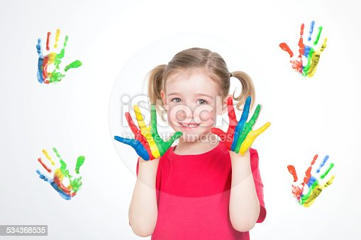 istock girl painting colourful handprints 534368535