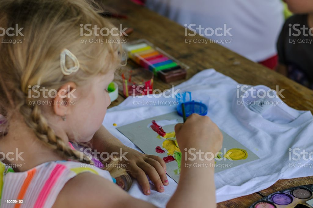 girl painting into t-shirt stock photo
