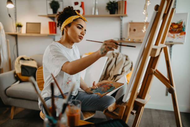 Girl painting on canvas Photo of young females artist in her apartment hobbies stock pictures, royalty-free photos & images