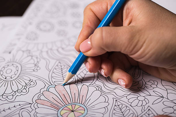 girl paints a coloring book for adults with crayons - mandala bildbanksfoton och bilder