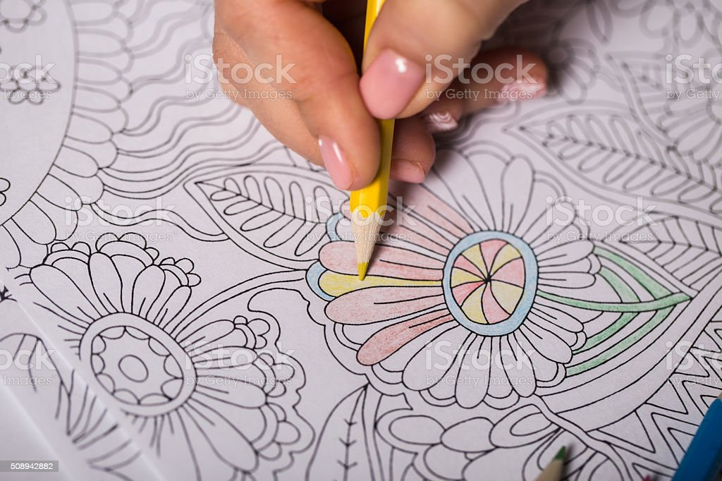 Girl paints a coloring book for adults with crayons stock photo