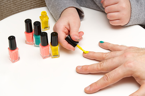 Girl paints her dad's nails with various colors. LGBT family concept. daughter have fun with dad