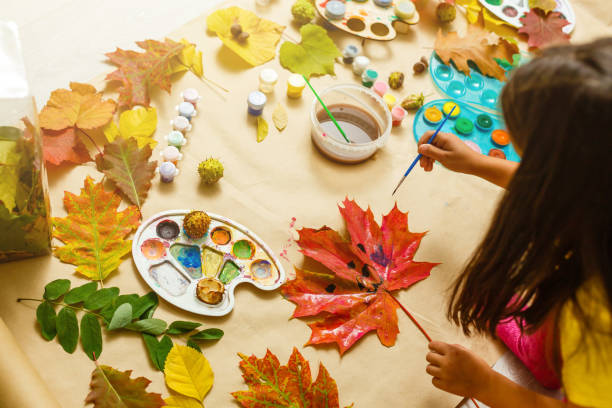 Girl paints leaves. Gouache, brush and various autumn leaves, Children's art project. Colorful Hand-painted on dry autumn leaves stock photo