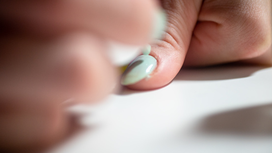 girl paints nails in green, close up.