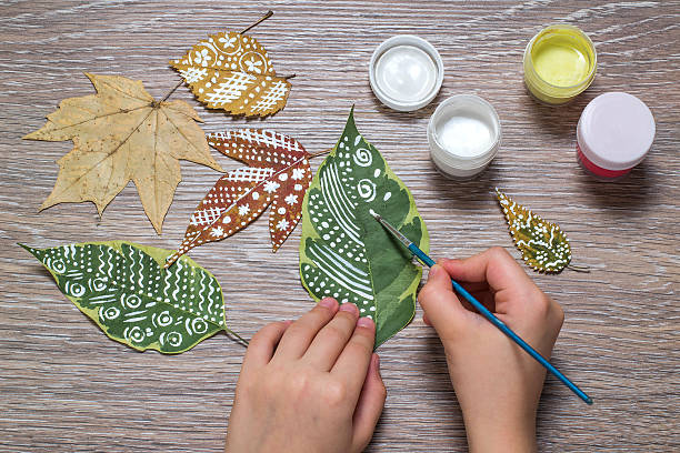 Girl paints patterns of dry autumn leaves stock photo