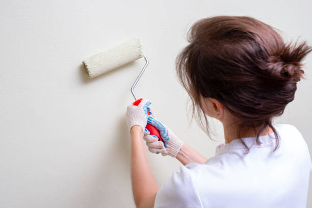 girl paints the wall paint roller stock photo