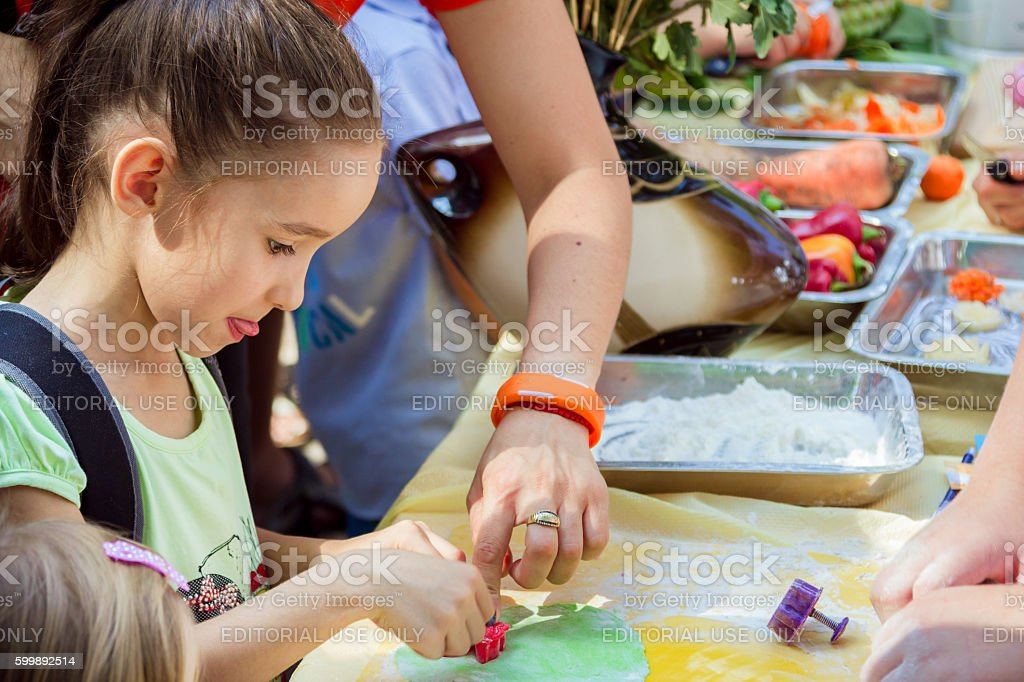Girl participating in cooking workshop making paste decorations - Photo