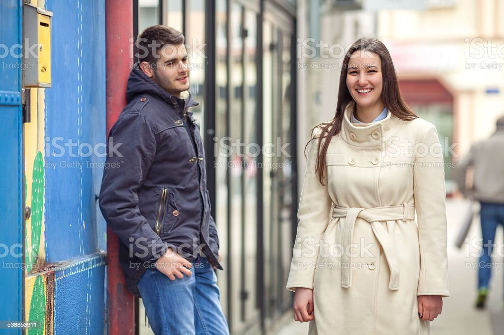 Girl Passing by Young Man on the Street stock photo